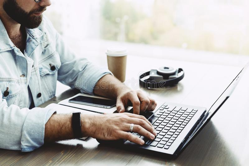 Closeup of male hands typing on computer keyboard. Bearded man uses laptop in cafe. Businessman working remotely stock photos