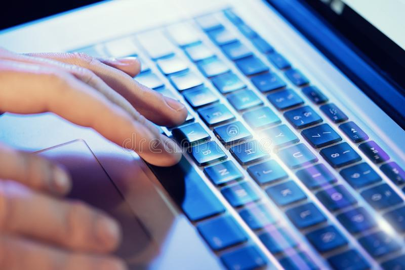 Closeup of male hands typing on laptop keyboard at the office. Visual effects, flares. stock images