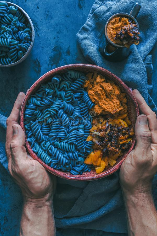 Closeup of a male holding a plate with vegan mermaid pasta in it royalty free stock photo