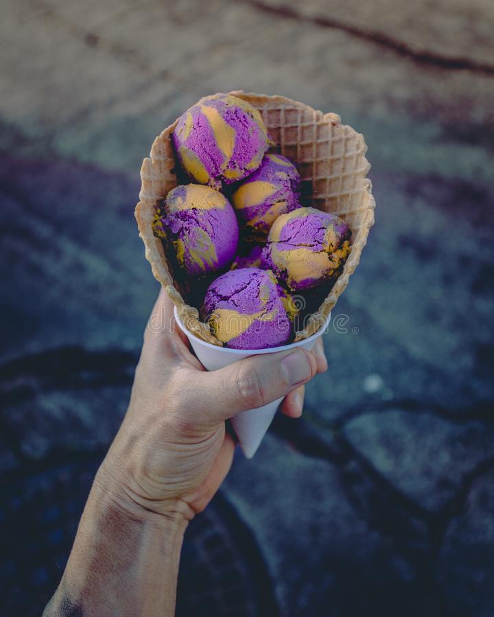Closeup of a male`s hand holding a waffle cone with colorful ice-cream in it royalty free stock photo