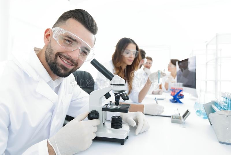 Closeup of male technician sitting at his working in the laboratory royalty free stock photography