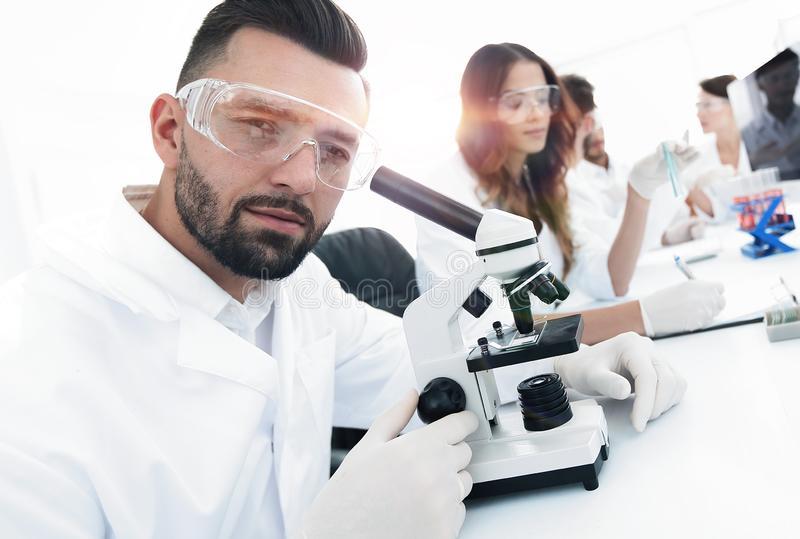 Closeup of male technician sitting at his working in the laboratory royalty free stock images