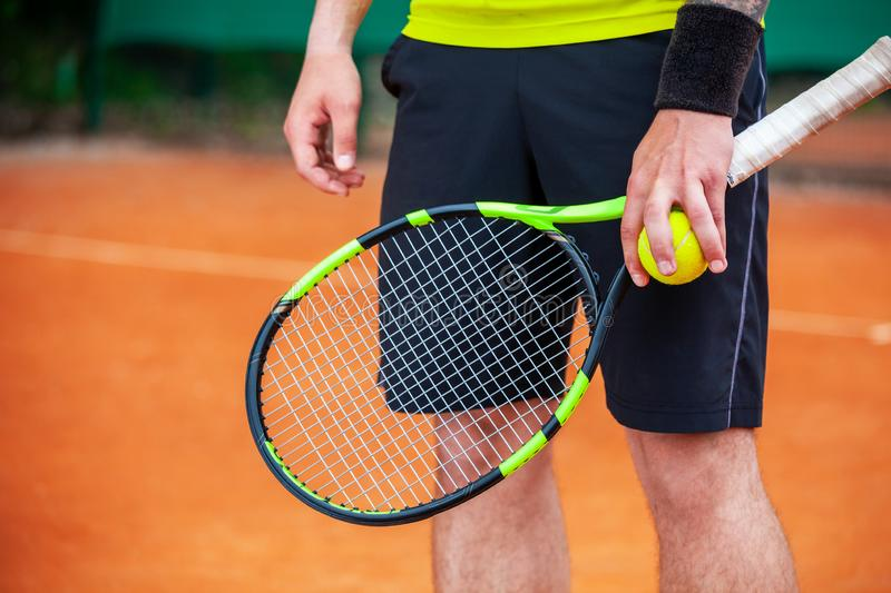 Closeup male tennis player holding racket and ball stock images