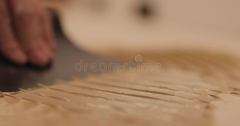 Closeup man applying polyurethane adhesive for parquet stock images