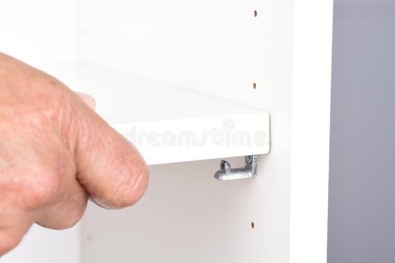 Closeup of a man assembling a DIY piece of furniture. The man is using a screwdriver to tighten a piece of hardware stock photos