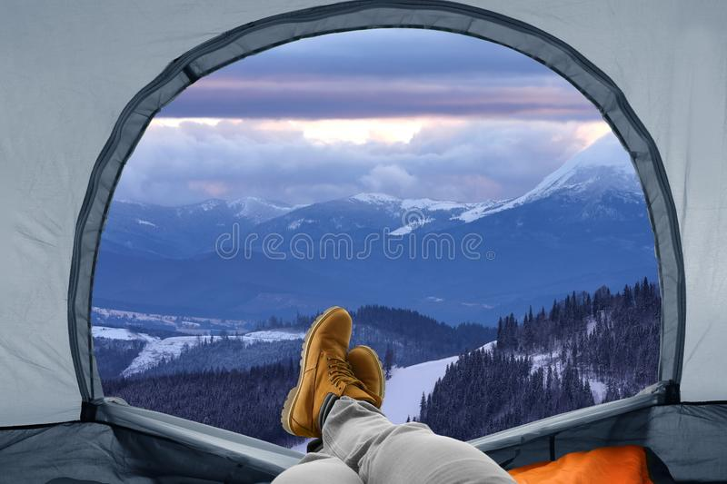 Closeup of man in camping tent on snowy mountain hill. View from inside stock images