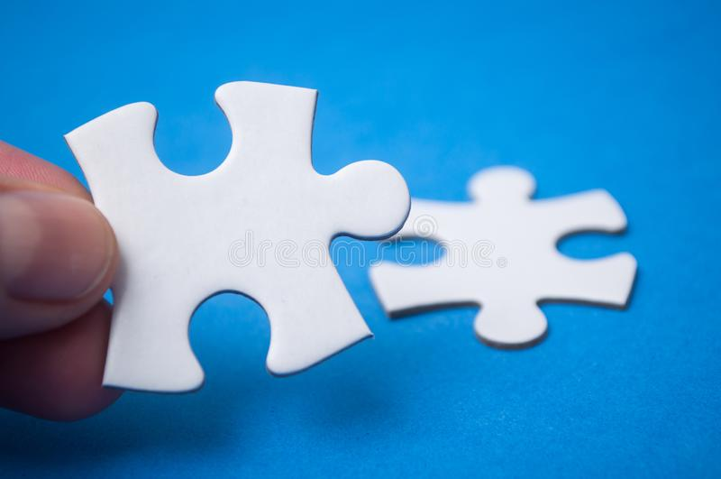 man connecting with hand two jigsaw puzzle pieces on blue background. The concept of finding the right solutions in stock images