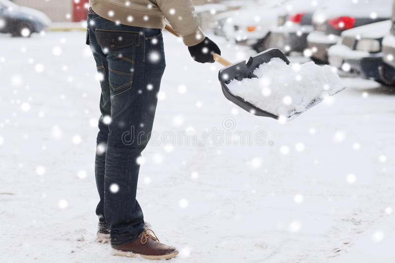 Closeup of man digging snow with shovel near car. Transportation, winter, people and vehicle concept - closeup of man digging snow with shovel near car royalty free stock photos