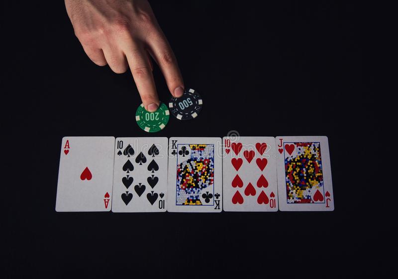 Closeup of man hand, poker player bluffing, as betting two chips. Playing at the casino gaming table, unknown cards combination royalty free stock photography