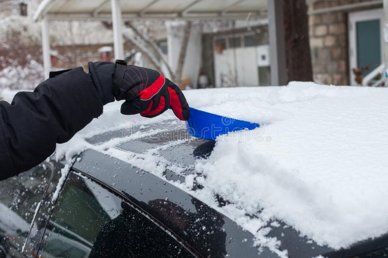Closeup of man hand in winter gloves clean snow from roof of the car with small shovel cold winter day stock image