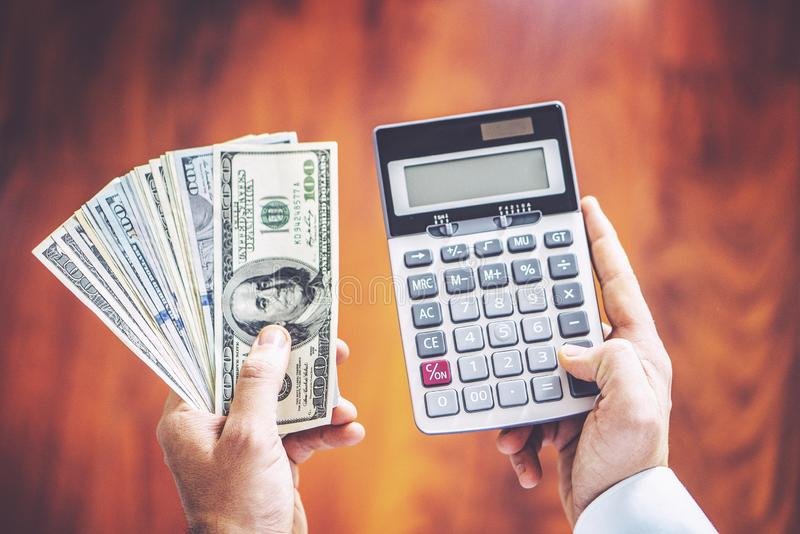 Closeup of man hands count us dollar mone, man has money in one hand and calculator in another royalty free stock photos