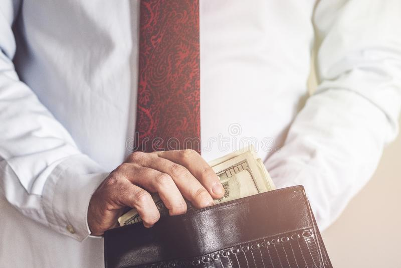 Closeup of man hands count us dollar money, male hand putting money in the wallet, light and business concept royalty free stock image