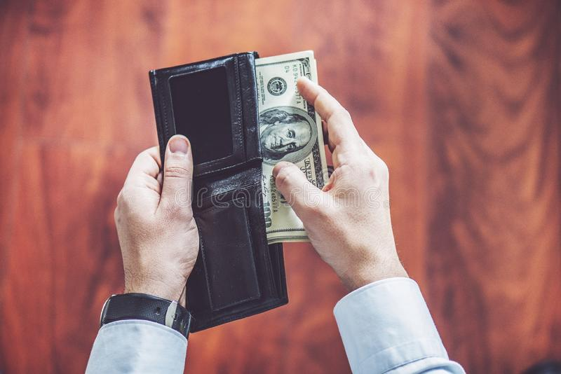 Closeup of man hands count us dollar money, male hand putting money in the wallet stock photo