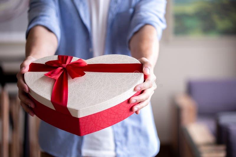 Closeup of man hands giving a present gift towards camera - holidays theme. Closeup of man hands giving a present gift towards camera - holidays theme stock image