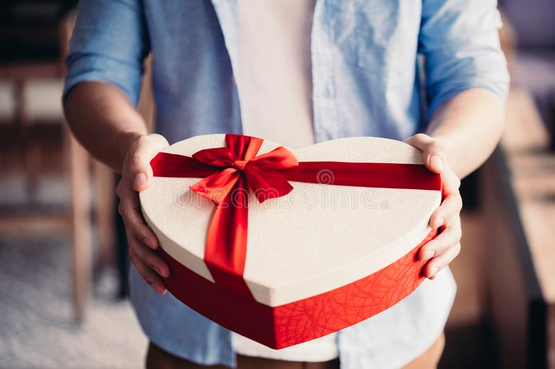 Closeup of man hands giving a present gift towards camera - holidays theme.  royalty free stock image