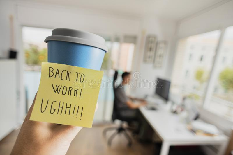 Man at office and text back to work. Closeup of a man having a cup of coffee in his hand, with a sticky note with the text back to work written in it, and a man stock photo