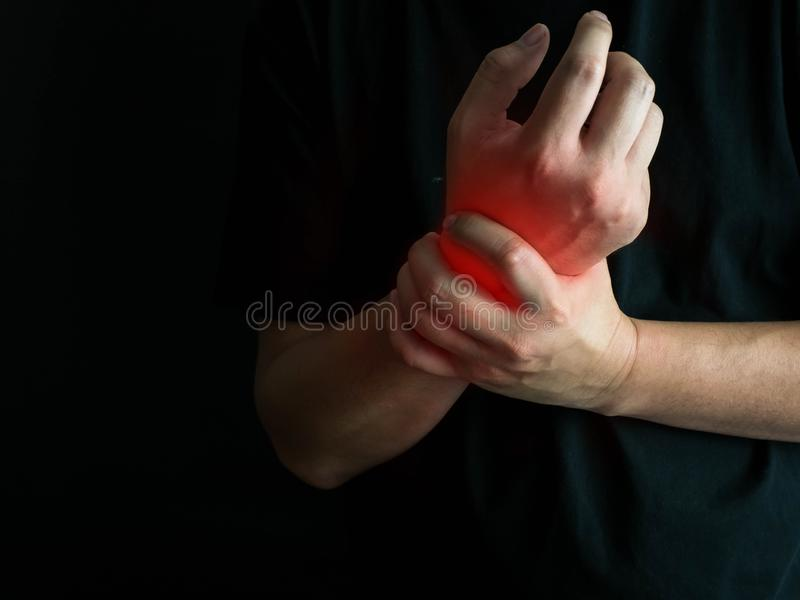 Closeup man holds he wrist hand injury, feeling pain. Health care and medical conept royalty free stock photos