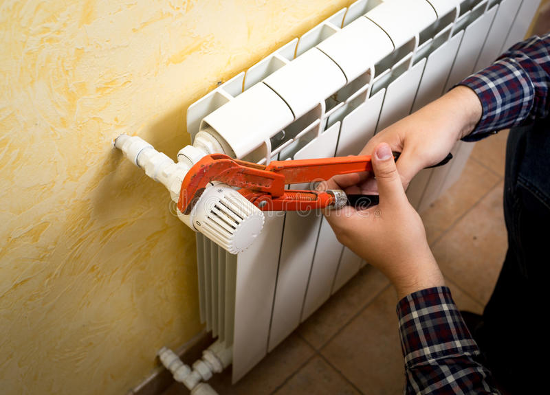 Closeup of man installing radiator valve with red plumber pliers royalty free stock photography