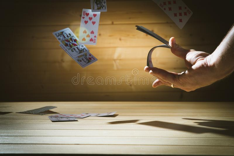 Closeup of man magician with two playing cards in his hand over grey background royalty free stock photography