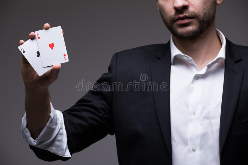 Closeup of man magician with two playing cards in his hand royalty free stock images