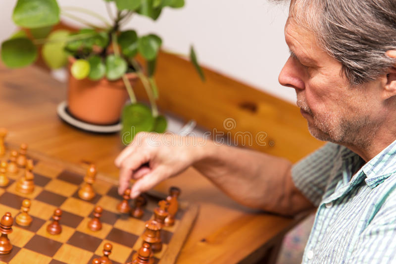 Closeup, man is playing chess. Closeup, senior adult is playing chess royalty free stock photography