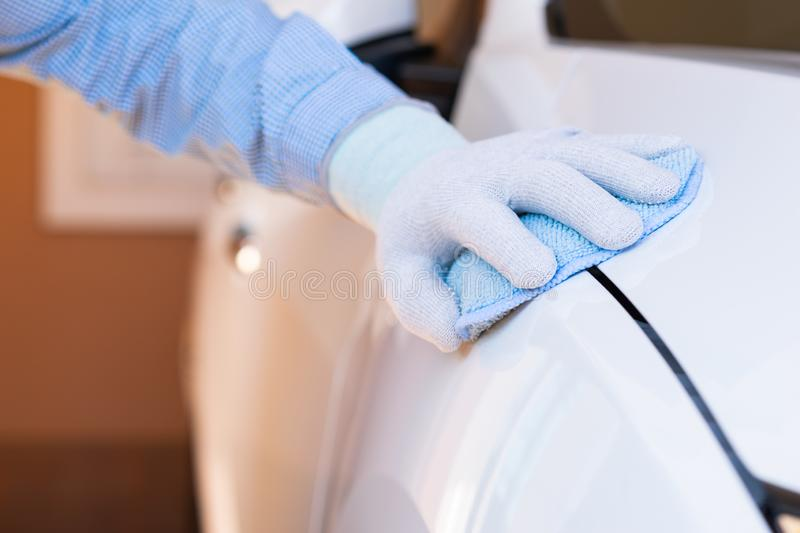 Closeup for man polishing cleaning car with microfiber cloth royalty free stock images