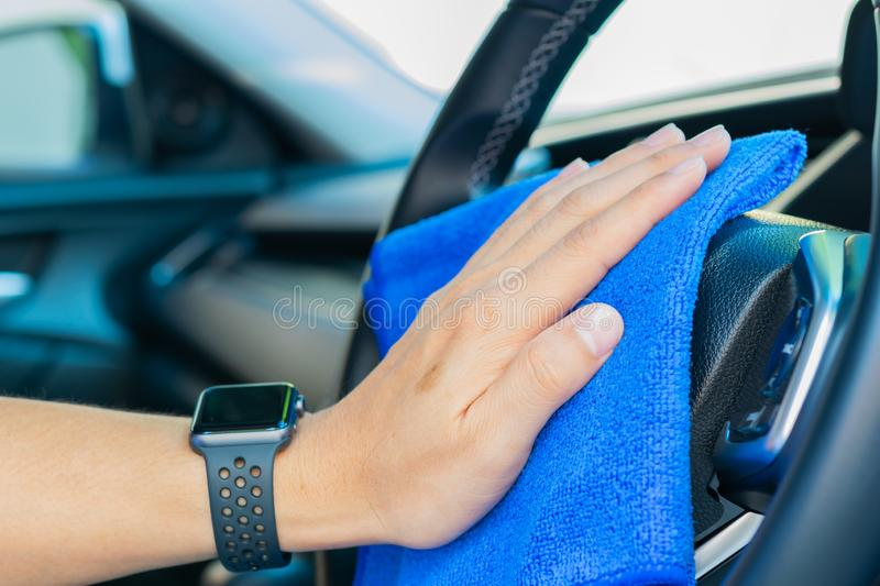 Closeup for man polishing cleaning car steering wheel with microfiber cloth stock photography