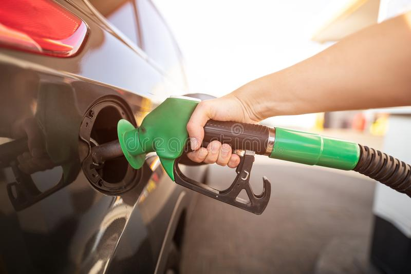 Closeup of man pumping gasoline fuel in car at gas station stock images