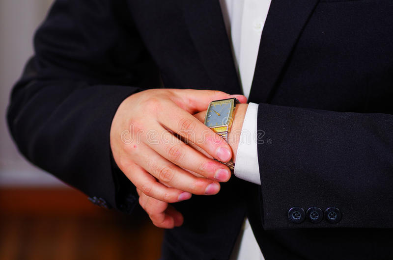 Closeup man's arm wearing suit, adjusting silver wrist watch using hands, men getting dressed concept royalty free stock images