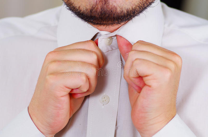 Closeup man's chest wearing white shirt, tying tie using hands, face partly visible, men getting dressed concept royalty free stock photos