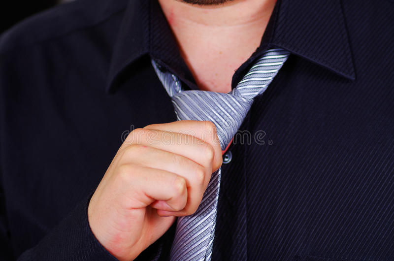 Closeup man's chest wearing white shirt, tying tie using hands, face partly visible, men getting dressed concept stock photography