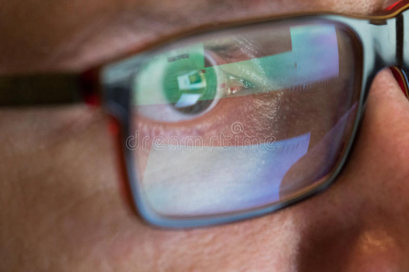 Closeup man`s eye in glasses works on laptop at night royalty free stock images