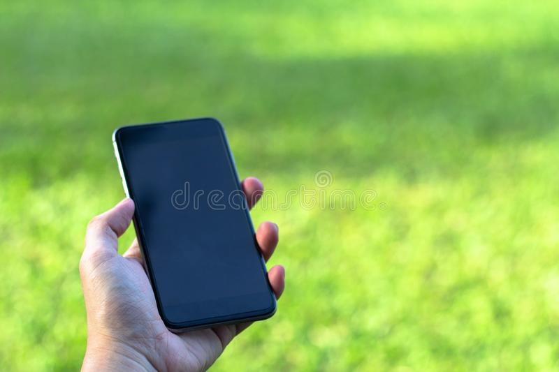 Closeup of man hand holding and using smart phone with blank screen on outdoor park. stock photos