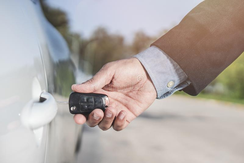 Closeup of a man`s hand inserting a key into the door lock of a car. Horizontal format. Car and man are unrecognizable royalty free stock photo