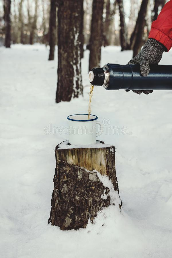 Closeup of man`s hand in knitted glove pouring hot beverage into white enamel cup. On a tree stub outdoors, selective focus stock photo