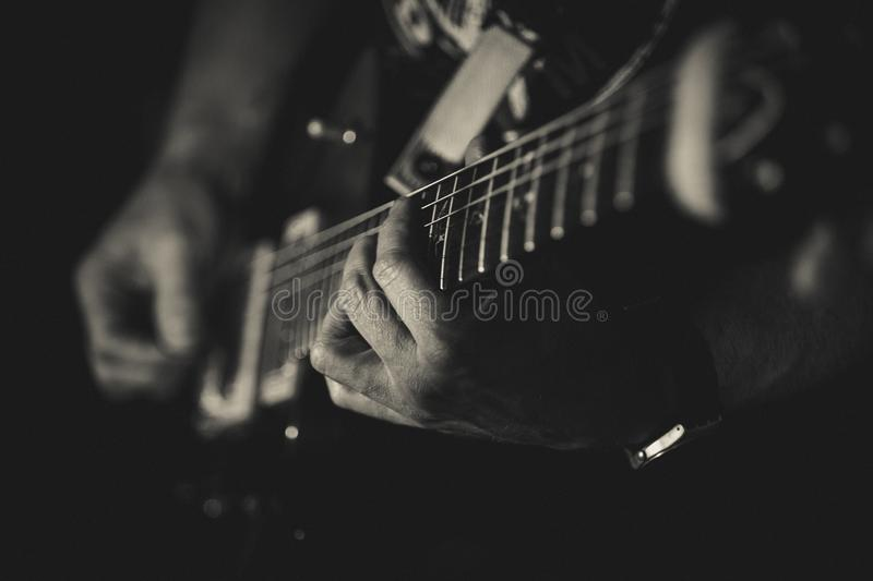 Closeup of man`s hands playing guitar on the concert. Guitarist. Monochrome. Music concept.  royalty free stock photo