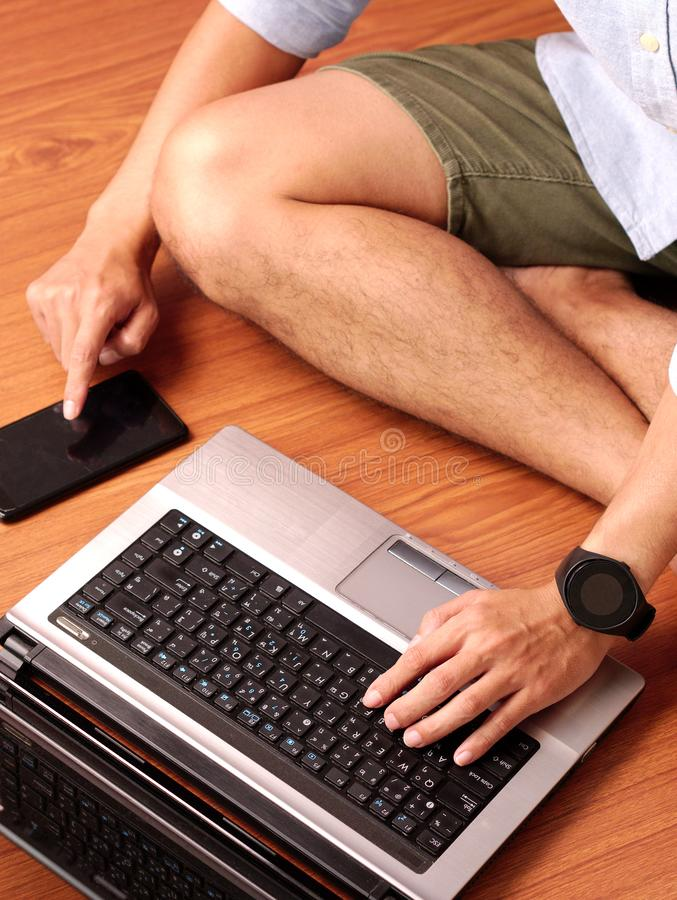 Closeup of a man sitting typing on keybord of his laptop and his smartphone simultaneously. Closeup of a man sitting on wooden floor and typing on keybord of stock photo