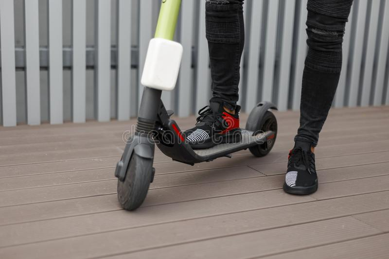 Closeup of man trendy legs in a black jeans in fashionable sneakers on a electric scooter. Stylish guy stands on a modern scooter. In the city near metallic royalty free stock photos