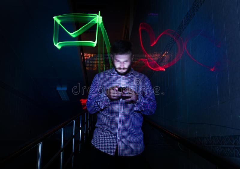 Closeup of a man using mobile phone night time with long exposure icons royalty free stock photography