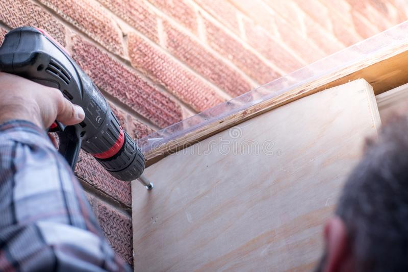 Man Using a Power Drill building a house porch at home in a sunny day stock photo