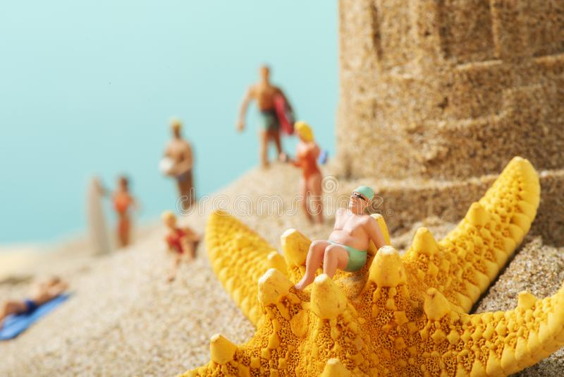 Miniature people in swimsuit on the beach stock photo