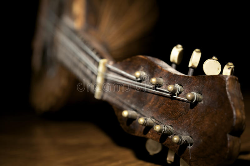 Closeup of mandolin. Closeup of old mandolin lying on wooden board and black background royalty free stock photos