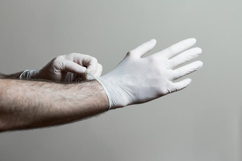A closeup of a mans hands putting on latex gloves.  royalty free stock images