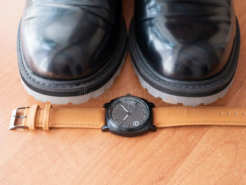 Closeup of mans wrist watch by pair of stylish elegant black classic shoes.  royalty free stock image
