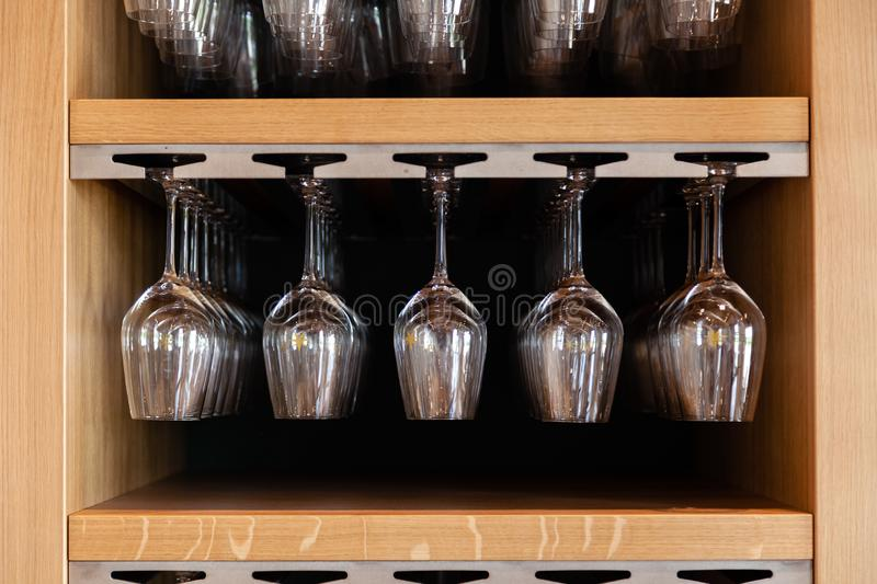Closeup many upside down empty clear transparent crystal upturned wine glasses hanging in straight row on brown wooden shelf, rack stock photo