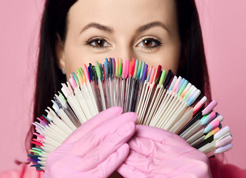 Closeup. Master in pink medicine gloves keeps with nail varnish samples display on background. Closeup. Nail technician in pink medicine gloves keeps with nail stock image