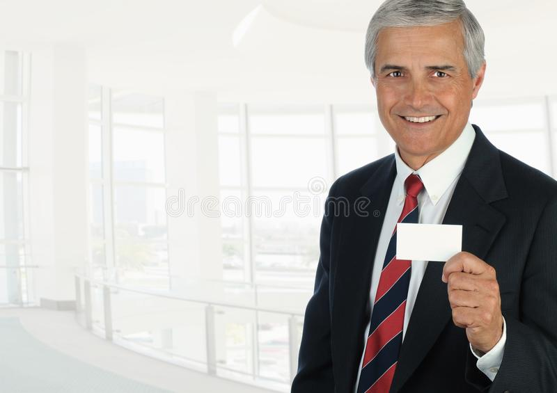 Mature businessman in high key office setting holding a blank business card royalty free stock image