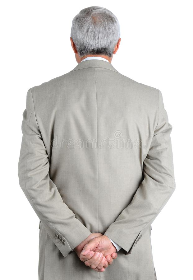 Closeup of a mature, businessman seen from behind with his hands clasped behind his back stock photography