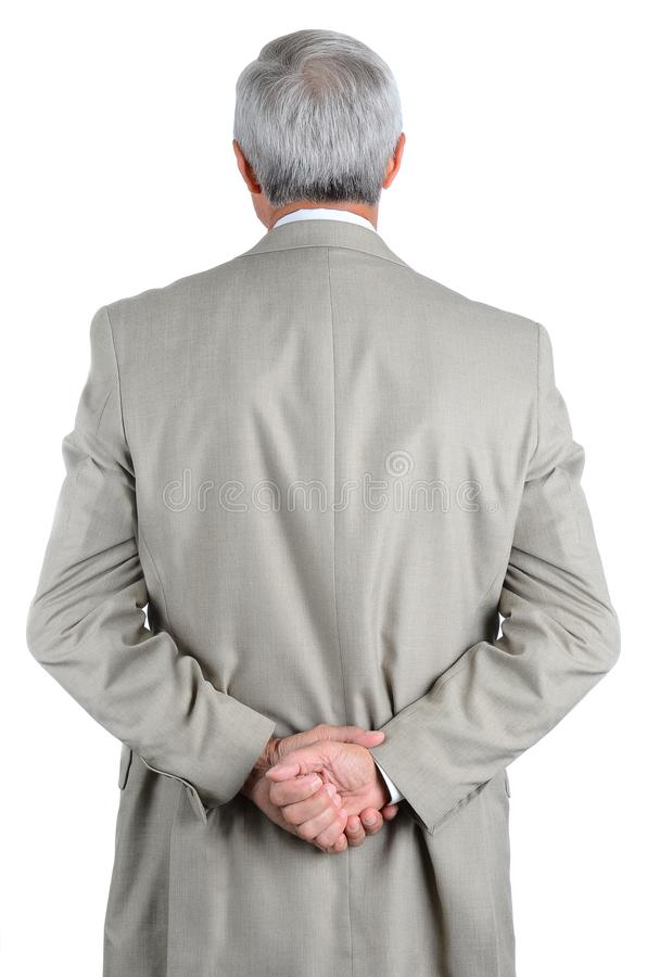 Closeup of a mature, businessman seen from behind with his hands clasped behind his back royalty free stock images