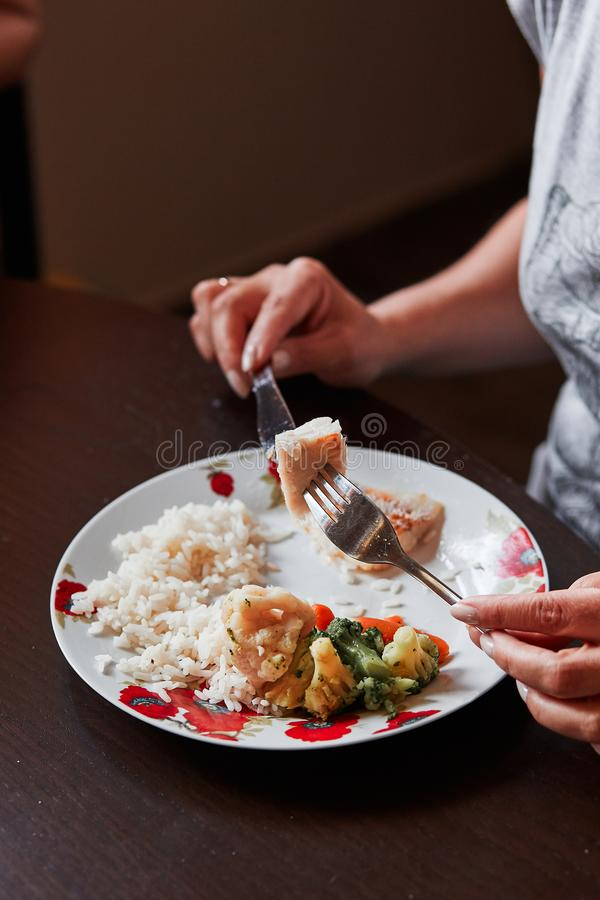 Closeup of the meal on plates on table and hands holding cutlery. People having a dinner at home royalty free stock images